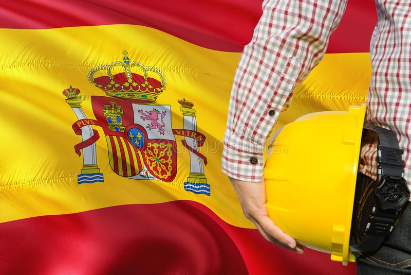 Hiszpańszczyzny Konstruują trzymają żółtego zbawczego hełm z machać Hiszpania chorągwianego tło Budowy i budynku poj?cie zdjęcie royalty free