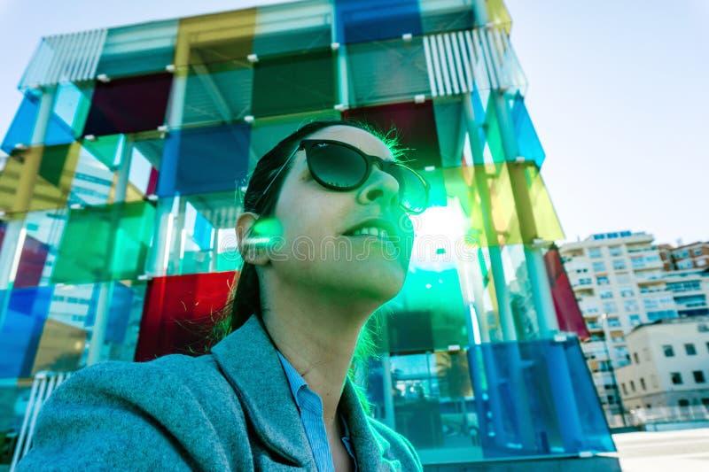 Hiszpania, Malaga - 04 04 2019: Kobieta abstrakcjonistyczny portret w rayban okularach przeciwsłonecznych obok kolorowy sześcianu fotografia stock