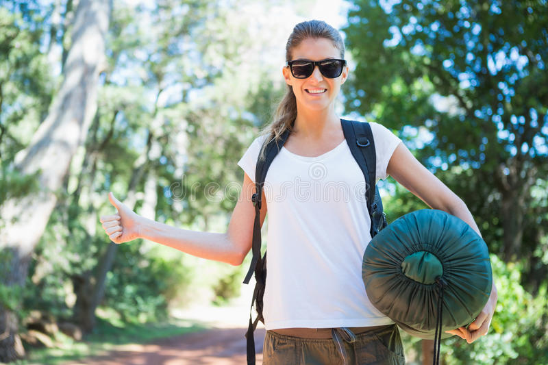 Hitch hiking woman with sleeping bag royalty free stock image