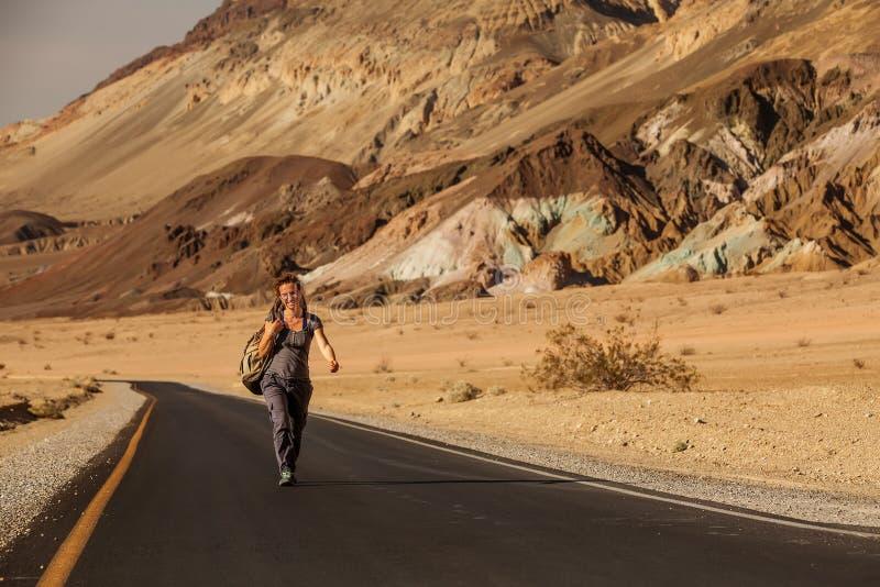 Hitchhiker γυναίκα που περπατά σε έναν δρόμο στις ΗΠΑ στοκ φωτογραφία