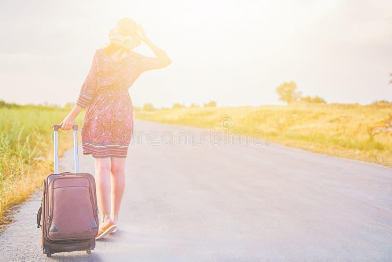 Hitchhiker γυναικών με τη βαλίτσα στοκ εικόνα