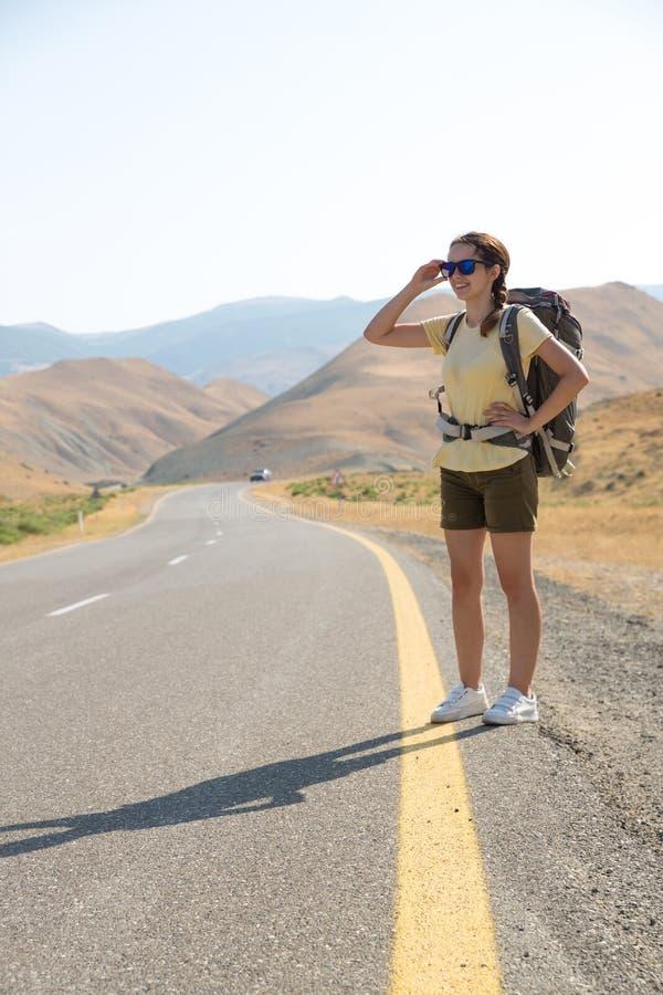 Hitchhiker ταξιδιωτική γυναίκα στο δρόμο στο ηλιοβασίλεμα Ταξιδιωτικός οδοιπόρος κοριτσιών στο δρόμο r Ελευθερία στοκ εικόνες
