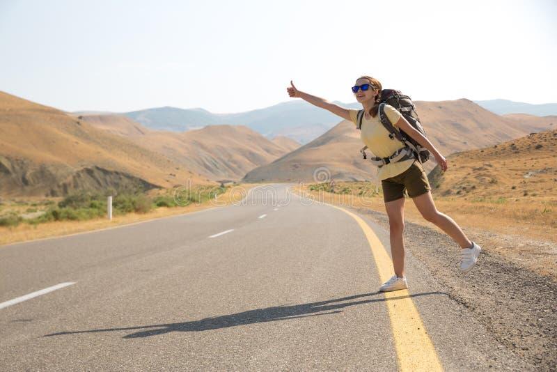 Hitchhiker ταξιδιωτική γυναίκα στο δρόμο στο ηλιοβασίλεμα Ταξιδιωτικός οδοιπόρος κοριτσιών στο δρόμο r Ελευθερία στοκ φωτογραφία