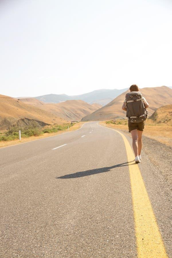 Hitchhiker ταξιδιωτική γυναίκα στο δρόμο στο ηλιοβασίλεμα Ταξιδιωτικός οδοιπόρος κοριτσιών στο δρόμο r Ελευθερία στοκ φωτογραφία με δικαίωμα ελεύθερης χρήσης
