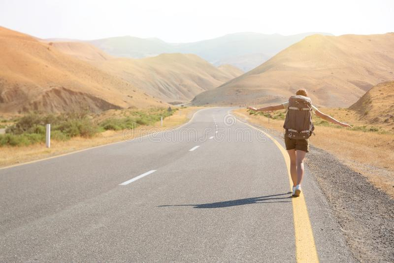 Hitchhiker ταξιδιωτική γυναίκα στο δρόμο στο ηλιοβασίλεμα Ταξιδιωτικός οδοιπόρος κοριτσιών στο δρόμο r Ελευθερία στοκ εικόνα με δικαίωμα ελεύθερης χρήσης