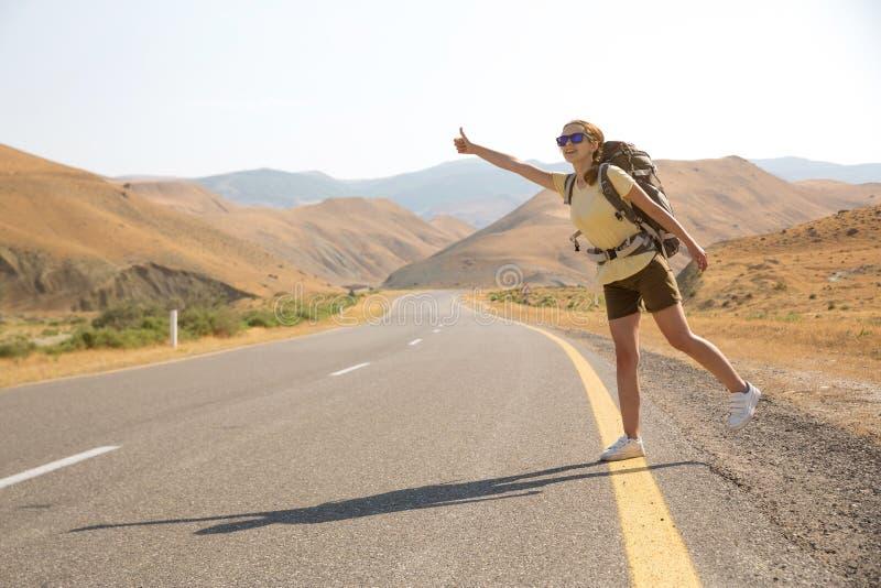 Hitchhiker ταξιδιωτική γυναίκα στο δρόμο στο ηλιοβασίλεμα Ταξιδιωτικός οδοιπόρος κοριτσιών στο δρόμο r Ελευθερία στοκ εικόνα