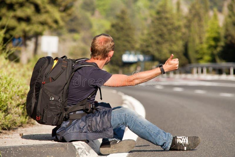 Hitchhiker ταξιδιωτική συνεδρίαση ατόμων στην άκρη του δρόμου στοκ φωτογραφία