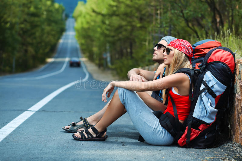 Hitchhiker. Two young people tourists hitchhiking along a road royalty free stock images