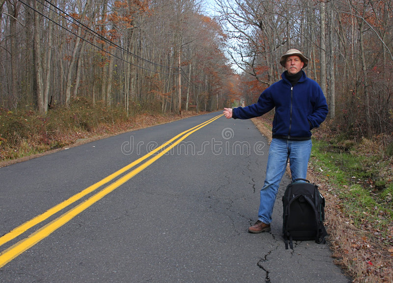 Hitchhiker. Man Hitchhiking On A Country Road in fall stock photography