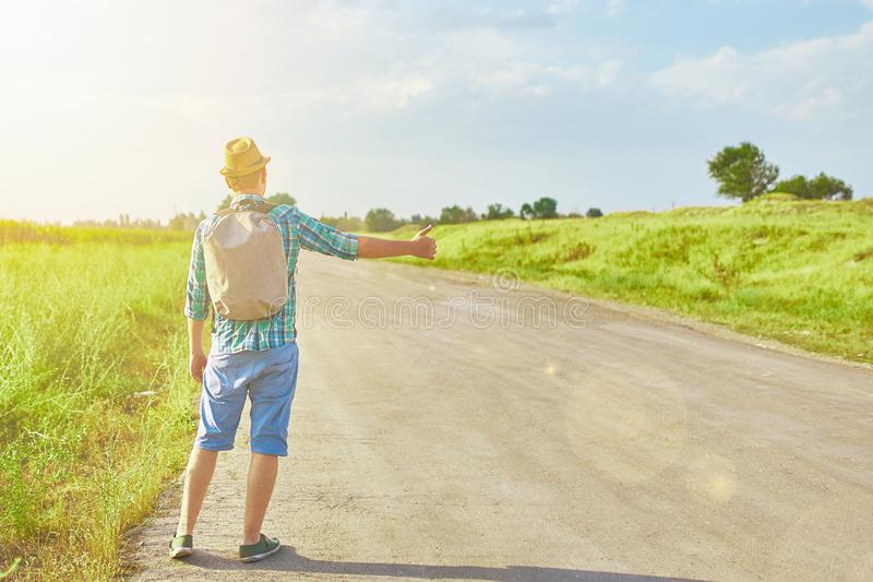 Tropic hitchhiker. Hitchhiker with backpack in summer hat, light shirt, shorts on the road in tropical country in Sunny weather at summer royalty free stock image