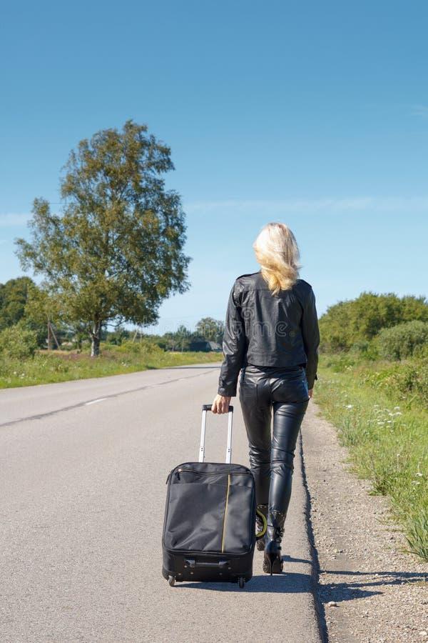Hitchhiker che cammina lungo una strada rurale immagine stock libera da diritti