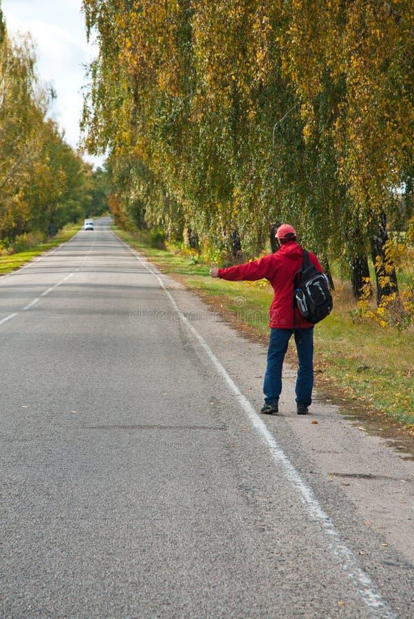 Hitchhiker maschio sulla strada di autunno fotografie stock