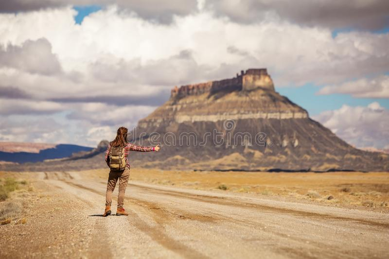 Hitchhiker woman walking on a road in USA.  royalty free stock photos