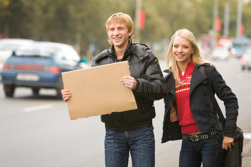 Hitchhikers. Photo of pretty girl and handsome guy hitchhiking on city road stock images