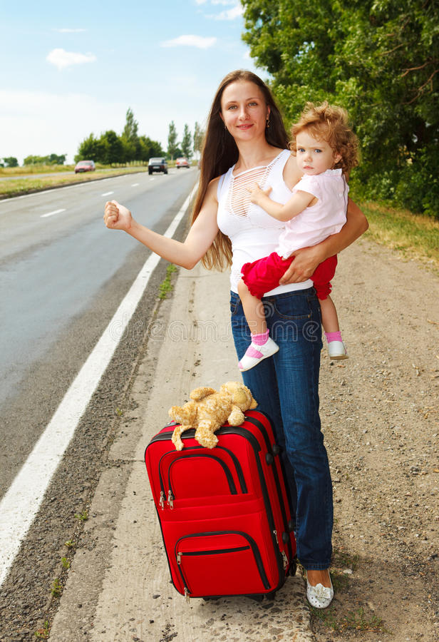 Hitchhiking. Mum and daughter on the road, hitchhiking royalty free stock image
