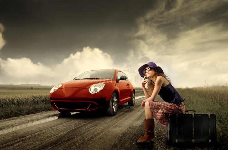 Hitchhiking. Woman sitting on a suitcase and a sport car running stock images