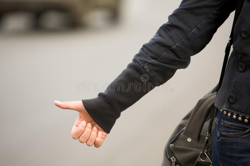 Hitchhiking. Close-up of female hand gesture of hitchhiking outside stock photo
