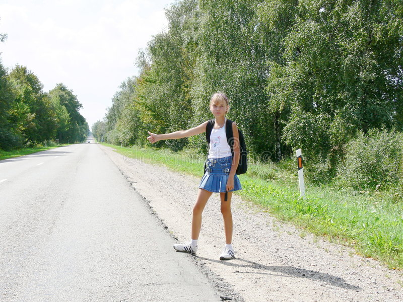 Hitchhiking. Young girl stock image