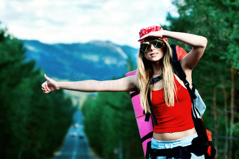 Hitchhiking. Pretty young woman tourist hitchhiking along a road stock photography