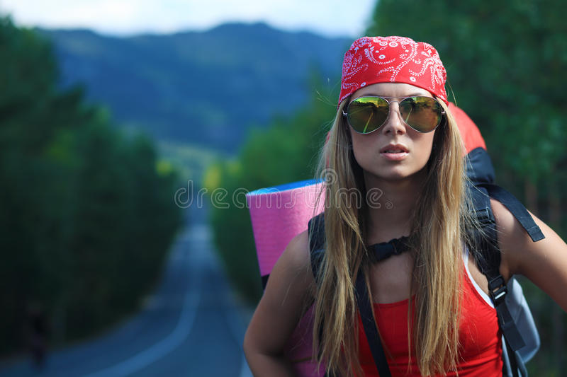 Hitchhiking. Pretty young woman tourist hitchhiking along a road royalty free stock photography