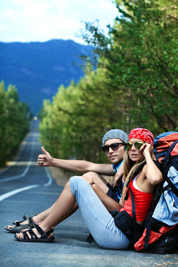 Hitchhiking. Two young people tourists hitchhiking along a road royalty free stock photo