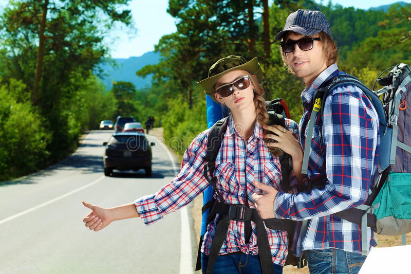 Hitchhiking. Two young people tourists hitchhiking along a road royalty free stock images