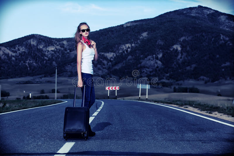 Hitchhiking. Attractive young woman hitchhiking along a road royalty free stock photography