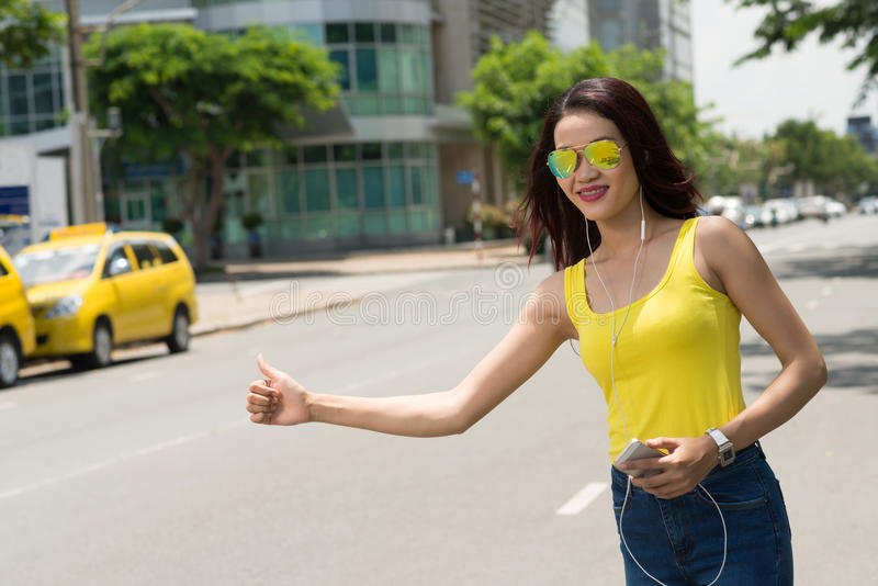 Hitchhiking. Attractive Vietnamese woman hitchhiking in the city stock photography