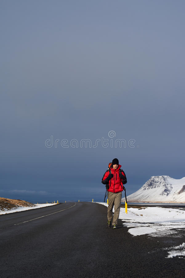 Hitchhiking backpacker in iceland. Backpacker travelling holiday on a budget hitchhiking for a ride on empty road, in harsh winter snowy cold extreme conditions royalty free stock photography
