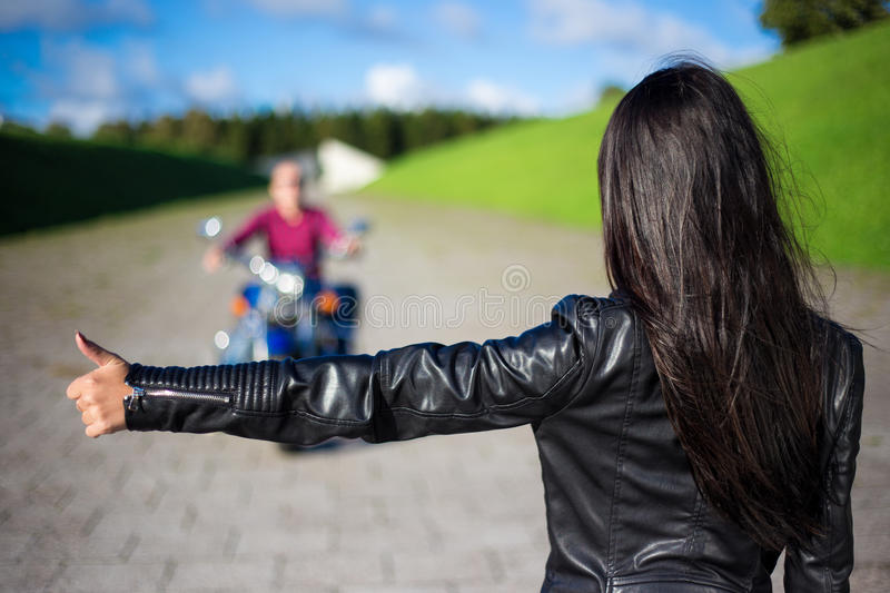 Hitchhiking concept - back view of woman hitching man on motorcycle on the road. Hitchhiking concept - back view of young women hitching men on motorcycle on the stock photos