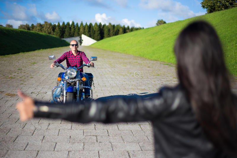 Hitchhiking concept - woman hitching man on motorcycle. Hitchhiking concept - women hitching men on motorcycle on the road royalty free stock image