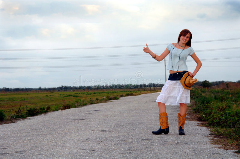 Hitchhiking country girl on rural road. A young women wearing a cowboy boots and hat hitchhiking alone on a country road royalty free stock photos