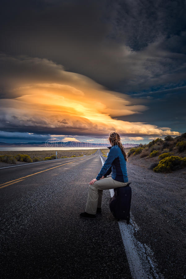 Hitchhiking on a desert road at sunset. Young woman hitchhiking with a suitcase on an empty road at sunset royalty free stock photos