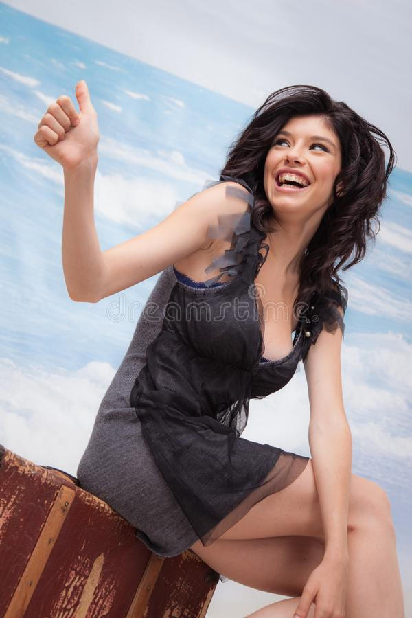 Hitchhiking Girl Laughing. Beautiful young girl is sitting on an old suitcase hitchhiking royalty free stock photos