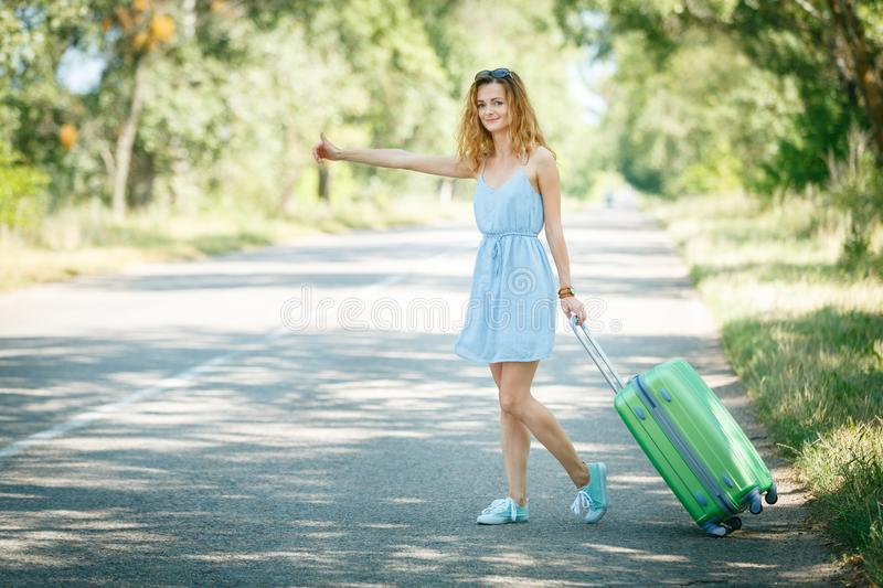 Hitchhiking girl looking for adventures. Hitchhiking girl in a light blue summer dress on a road with a green plastic case. Summer vacation road trip concept stock image