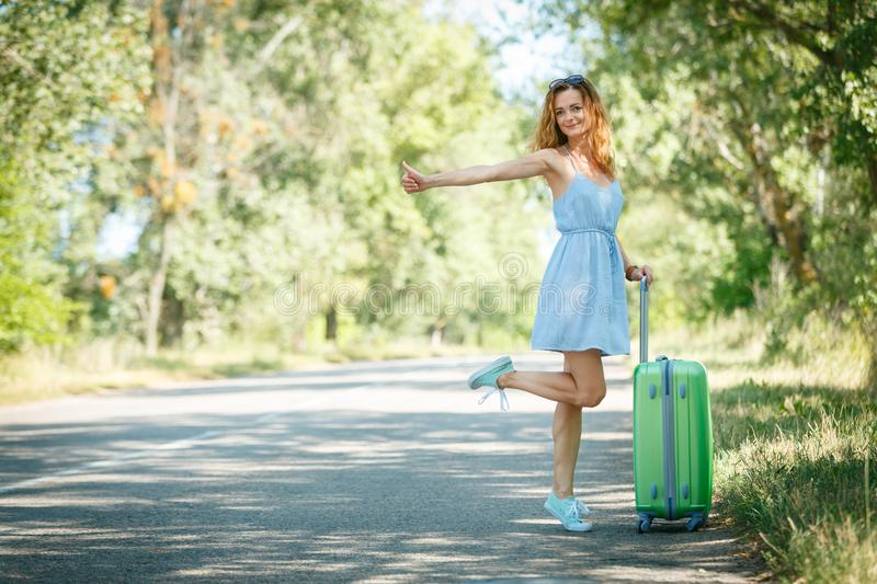 Hitchhiking girl looking for adventures. Hitchhiking girl in a light blue summer dress on a road with a green plastic case. Summer vacation road trip concept royalty free stock photography