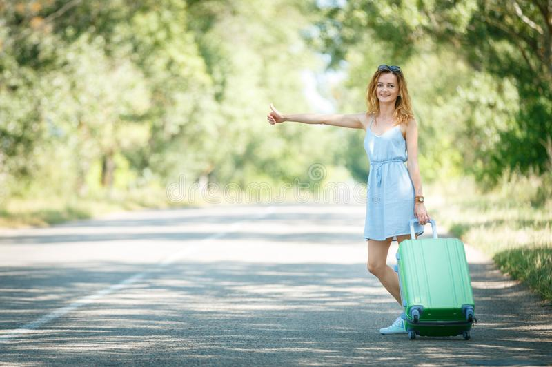 Hitchhiking girl looking for adventures. Hitchhiking girl in a light blue summer dress on a road with a green plastic case. Summer vacation road trip concept stock images
