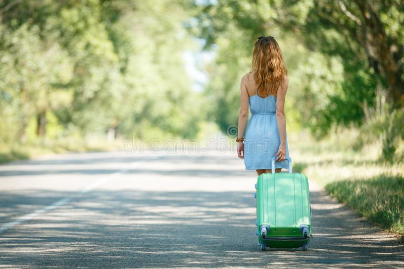 Hitchhiking girl looking for adventures. Hitchhiking girl shot from the back in a summer dress walking by the road with a green plastic case. Road adventure royalty free stock image