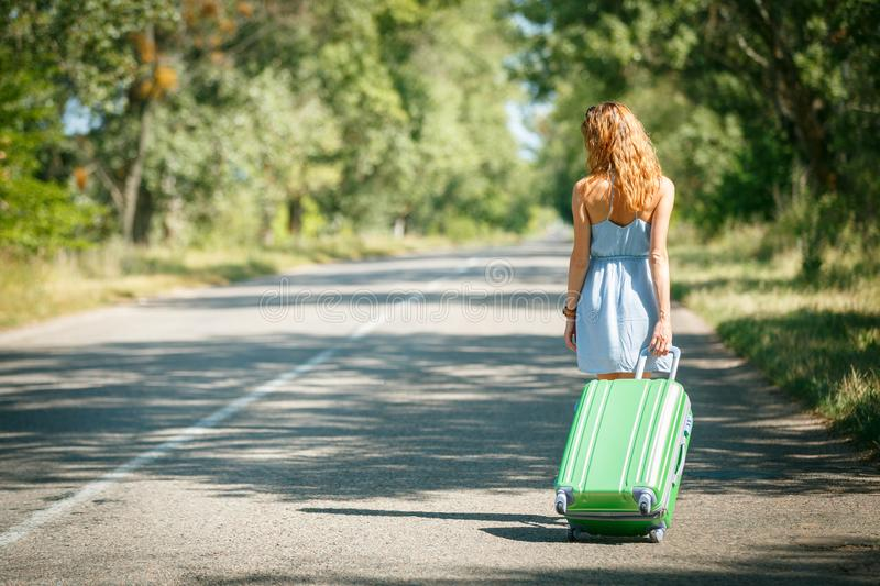 Hitchhiking girl looking for adventures. Hitchhiking girl shot from the back in a summer dress walking by the road with a green plastic case. Road adventure royalty free stock photography