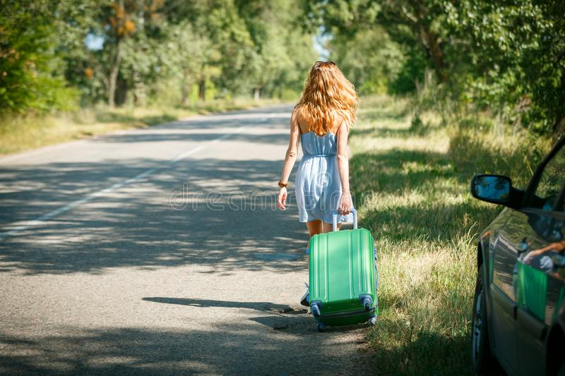 Hitchhiking girl looking for adventures. Hitchhiking girl shot from the back in a summer dress walking by the road with a green plastic case. Road adventure royalty free stock images
