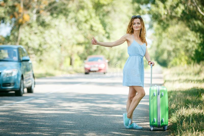Hitchhiking girl looking for adventures. Hitchhiking girl in a light blue summer dress on a road with a green plastic case. Summer vacation road trip concept royalty free stock photos