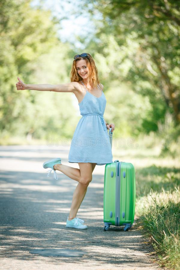 Hitchhiking girl looking for adventures. Hitchhiking girl in a light blue summer dress on a road with a green plastic case. Summer vacation road trip concept stock photo