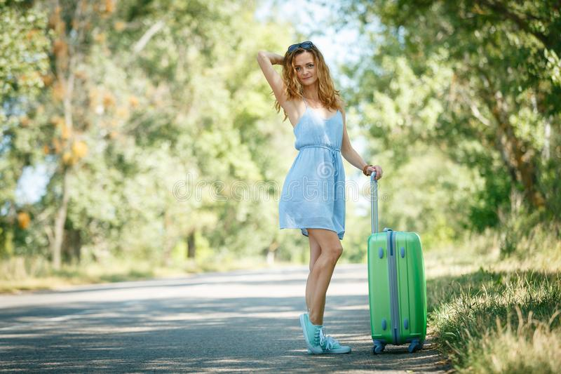 Hitchhiking girl looking for adventures. Hitchhiking girl in a light blue summer dress on a road with a green plastic case. Summer vacation road trip concept royalty free stock photo