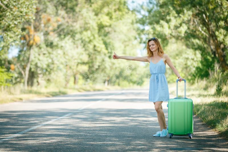 Hitchhiking girl looking for adventures. Hitchhiking girl in a light blue summer dress on a road with a green plastic case. Summer vacation road trip concept royalty free stock images
