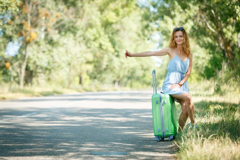 Hitchhiking girl looking for adventures. Hitchhiking girl in a light blue summer dress on a road with a green plastic case. Summer vacation road trip concept royalty free stock image