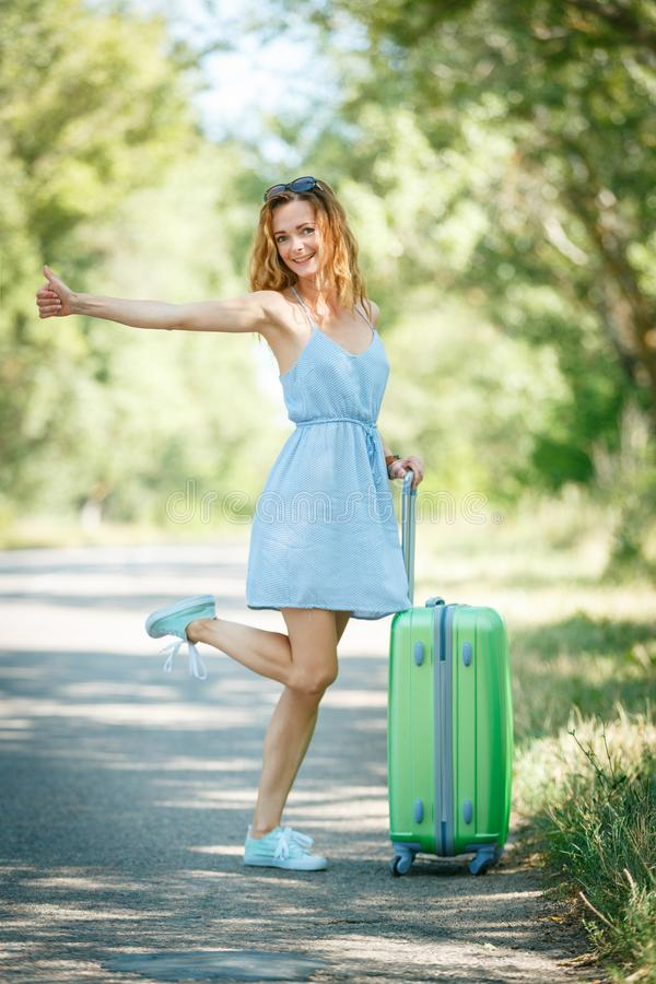 Hitchhiking girl looking for adventures. Hitchhiking girl in a light blue summer dress on a road with a green plastic case. Summer vacation road trip concept stock photos