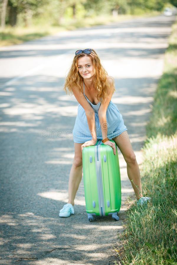 Hitchhiking girl looking for adventures. Hitchhiking girl in a summer dress on a road with a green plastic case. Road adventure concept stock photos