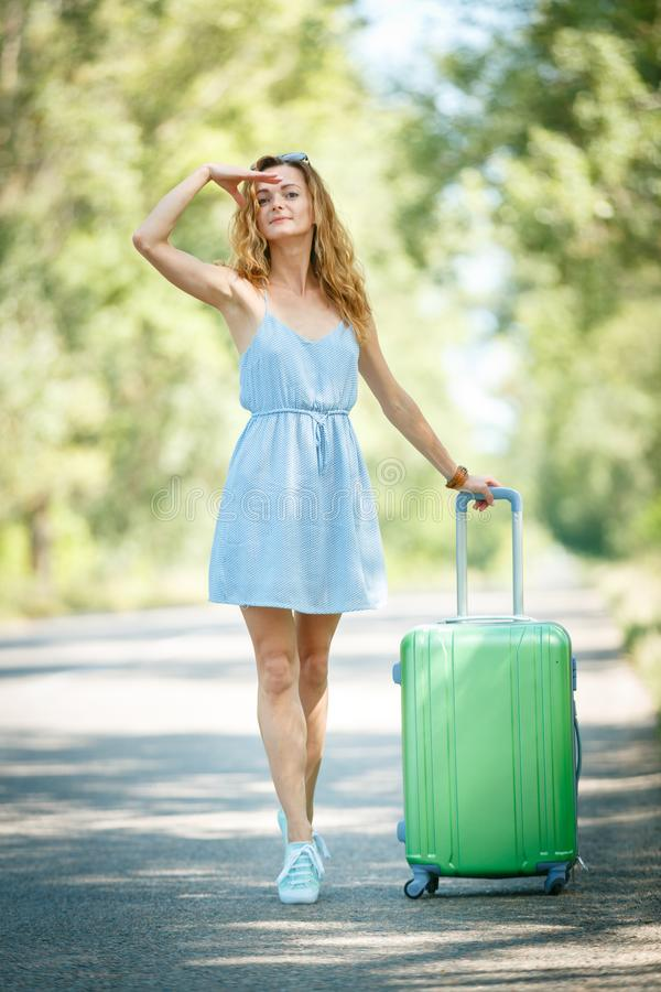 Hitchhiking girl looking for adventures. Hitchhiking girl in a summer dress on a road with a green plastic case. Road adventure concept stock photography