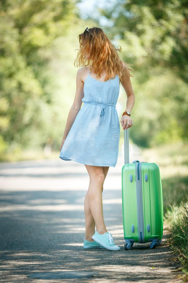 Hitchhiking girl looking for adventures. Hitchhiking girl in a summer dress on a road with a green plastic case. Road adventure concept stock image