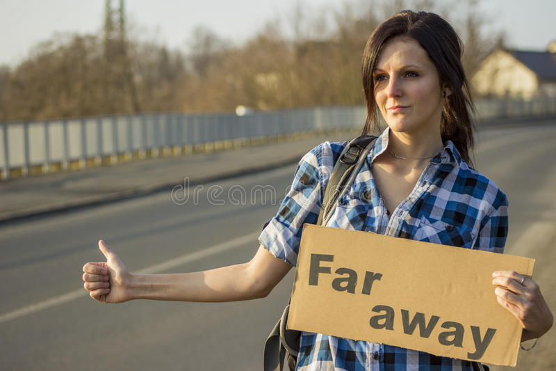 Hitchhiking girl on the road. Young girl is hitchhiking and wants to go far away royalty free stock photography